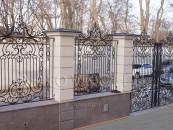 Кованый забор с поликарбонатом и коваными воротами на каменных столбах