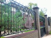 Кованый забор для частной территории с кирпичными столбами