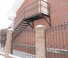 Металличесокая лестница с коваными перилами и кованый забор