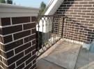 Ограждение кованое балкона с кирпичными столбами