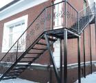 Угол металлической лестницы с коваными перилами