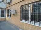 Кованые решетки на окнах первого этажа здания